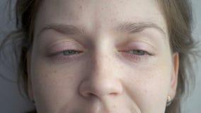 Blond kvinna som roterar hennes gröna ögon arkivfilmer