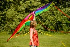 Blond kvinna som rymmer den färgrika draken Royaltyfri Foto