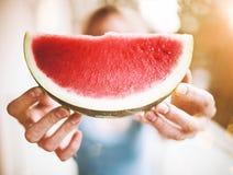 Blond kvinna som rymmer en skiva av den saftiga nya vattenmelon Royaltyfri Bild