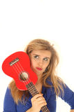 Blond kvinna som rymmer en ukulele till hennes framsida arkivbild