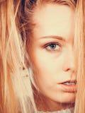 Blond kvinna som rymmer hennes långa tilltrasslade hår Arkivbild