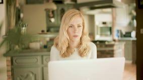 Blond kvinna som ser hennes bärbar dator som förvånas och chockas plötsligt lager videofilmer