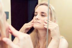 Blond kvinna som ser hennes reflexion royaltyfri foto