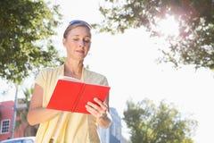 Blond kvinna som ser hennes resehandbok arkivfoto