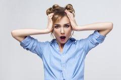 Blond kvinna som skriker med chock som rymmer händer på hennes huvud arkivbilder