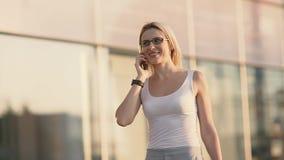 Blond kvinna som talar på telefonen lager videofilmer