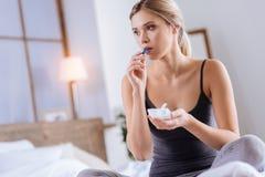 Blond kvinna som tar en blå kapsel, medan sitta på säng royaltyfri bild