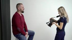 Blond kvinna som tar fotoet i studio av mannen lager videofilmer