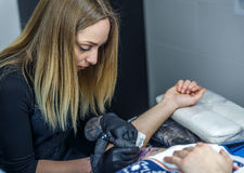 Blond kvinna som tatuerar en arm med mycket koncentration, Arkivfoton