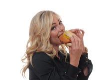 Blond kvinna som äter en smörgås Arkivbild