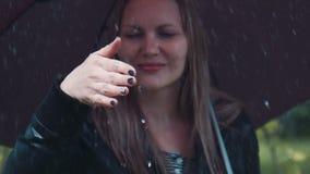 Blond kvinna som tycker om regn under det svarta vridande paraplyet stock video