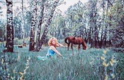 Blond kvinna som vilar i gräset Arkivbilder