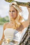 Blond kvinna under träd Arkivbild