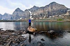 Blond kvinna vid den alpina sjön som tycker om bergsikten på en regnig dag Royaltyfri Bild