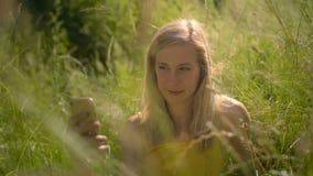Blond kvinnadet fria som tar en selfie med en mobiltelefon stock video
