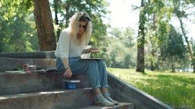 Blond kvinnakonstnär Painting en bild utomhus stock video
