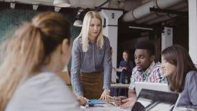 Blond kvinnalagledare som ger riktning till laget för blandat lopp av unga grabbar Idérikt affärsmöte på det moderna kontoret lager videofilmer