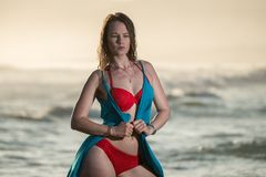 Blond kvinnasimning i havet med en röd bikini Arkivbild