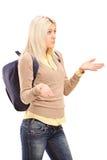 Blond kvinnlig deltagare med ryggsäcken som göra en gest - jag vet inte Royaltyfria Foton