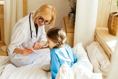 Blond kvinnlig doktor som visar en flicka indikatorerna på termometern royaltyfri foto