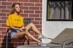 Blond kvinnlig modell Enjoying om dagen på pölen arkivfoto