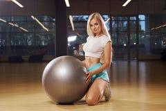 Blond kvinnlig modell som knäfaller och rymmer jämviktsbollen Royaltyfri Foto