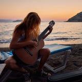 Blond kvinnlig som spelar den akustiska gitarren på stranden Royaltyfri Foto