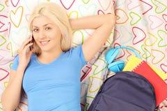 Blond kvinnlig student som ligger i säng och talar på en telefon royaltyfri fotografi