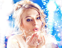 Blond lady blowing a magic dust Royalty Free Stock Image