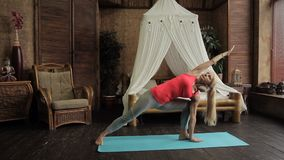 Blond lady is having yoga training in the morning in her bedroom. stock footage