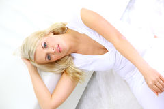 Blond lady laying in a bedroom Royalty Free Stock Photos