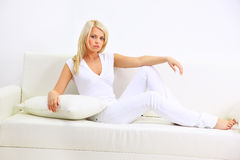 Blond lady laying in a bedroom Stock Images