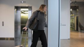 The blond lady is leaving the elevator and going to the reception after arriving from the trip. The businesswoman wears black classical trousers, gray jacket stock video