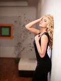 Blond lady model in black dress standing near wall Royalty Free Stock Photos