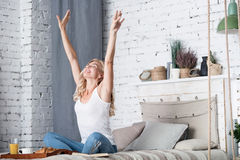 Blond lady is stretching on her bed in morning Stock Photo