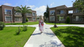 Blond lady walking along walkway. stock video footage