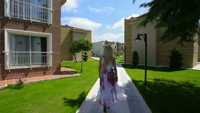 Blond lady walking near houses. stock video footage