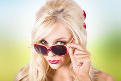 Blond lady wearing UV protective sunshades outside. Face of a fashionable blonde lady wearing UV protection sunglasses outside Stock Photography