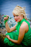 Blond on lake shore. A view of a pretty blond woman in a green dress, sitting among rocks on the seashore Royalty Free Stock Photos