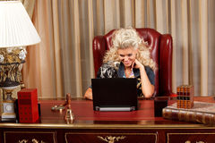 Blond and laptop. Stylish blond working on a laptop at the wooden desk Stock Photography