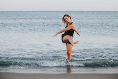 Blond le kvinna som ut plaskar vatten på stranden Arkivfoton