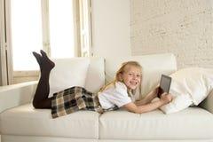 Blond liten flicka som ligger på den hem- soffasoffan genom att använda internet app på det digitala minnestavlablocket på det di Arkivbild