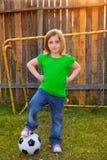 Blond liten flickafotbollspelare som är lycklig i trädgård Arkivbild