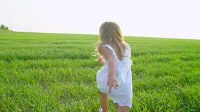 Blond liten gullig flicka i vit klänningspring på det grönt fältet och le Barn, ungespring i trädgårds- och skratta stock video