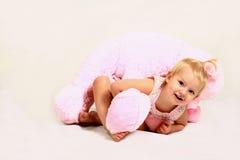 Blond litet barnflicka med det välfyllda djur Royaltyfria Foton