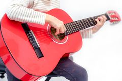 Blond litle girl sits and plays the red guitar royalty free stock photo