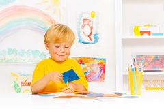 Blond little boy cutting cardboard shape in class Royalty Free Stock Images