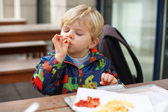 Blond little boy eating french fries in outdoor restaurant Royalty Free Stock Photos