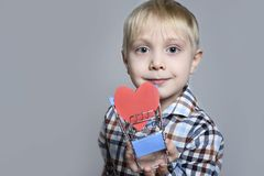 Blond little boy holding a metal shopping trolley with a heart shaped postcard inside.  royalty free stock photography