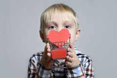 Blond little boy holding a metal shopping trolley with a heart shaped postcard inside.  stock photos